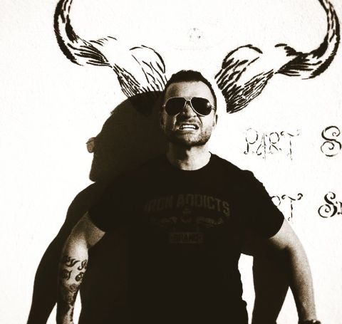 Nick E. Tarabay posing in front of camera in a black t-shirt and black spectacles.