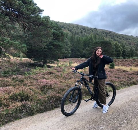 Nittha Jirayungyurn poses a picture while cycling at Scotland in black top and tracks.