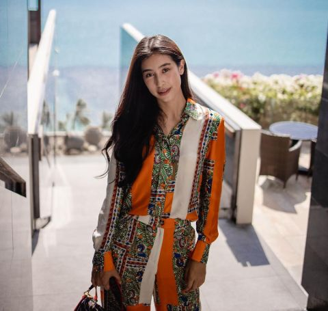 Chalida Vijitvongthong in a orange-white designer cloth in front of an ocean.
