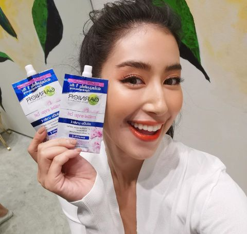 Chalida Vijitvongthong in a white top holds Garnier products in their promotion campaign.