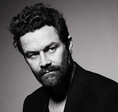 Björn Hlynur Haraldsson with dark beard looks across the camera, in a black coat.