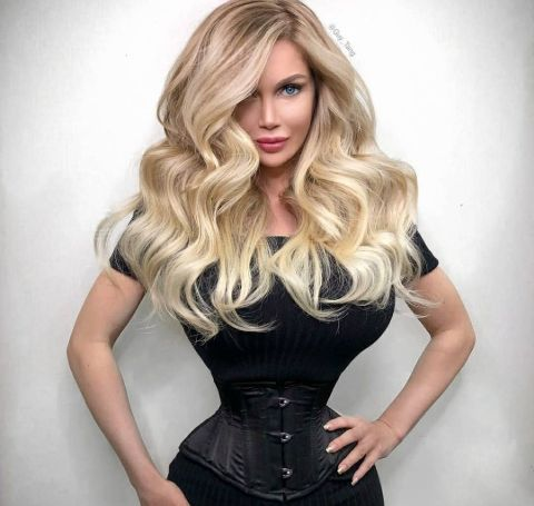 Pixee Fox in a black dress and blonde hair shows her 14-inch waist.