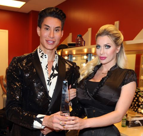 Pixee Fox in black dress, blonde hair poses with Justin Jedlica, on a black shiny coat and white shirt.