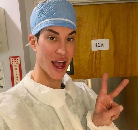 Justin Jedlica in doctor's gaun covering his head shows victory sign.