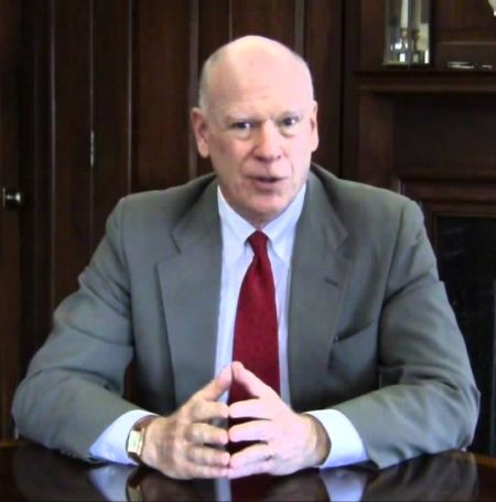 Knight Kiplinger all suited up and wearing red tie pictured at a meeting desk.
