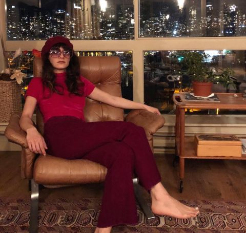 Sheila Vand in a red cap, tshirt and trouser posing at a sofa.