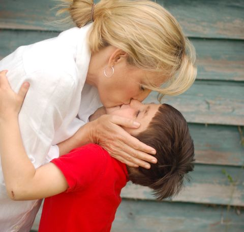 Sylvia Jefferies in white shirt kissing her child in red tshirt.