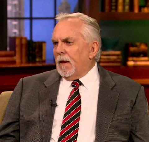 John Ratzenberger in a brown suit, white shirt and red tie.