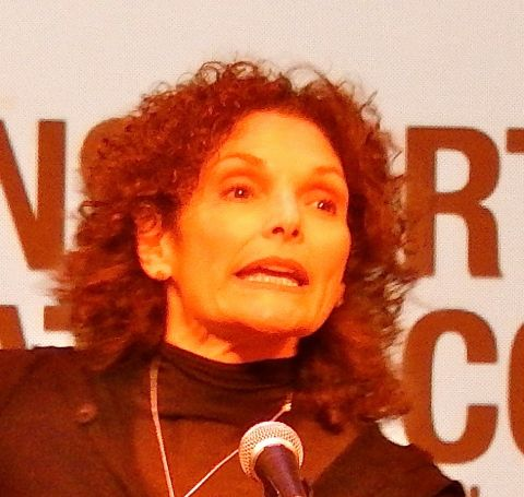 Mary Elizabeth Mastrantonio  in a black dress speaking with mike in front.