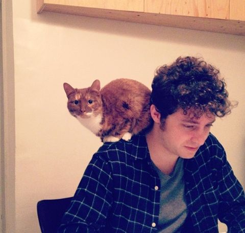 Kyle Soller in a black shirt with cat on his shoulders.