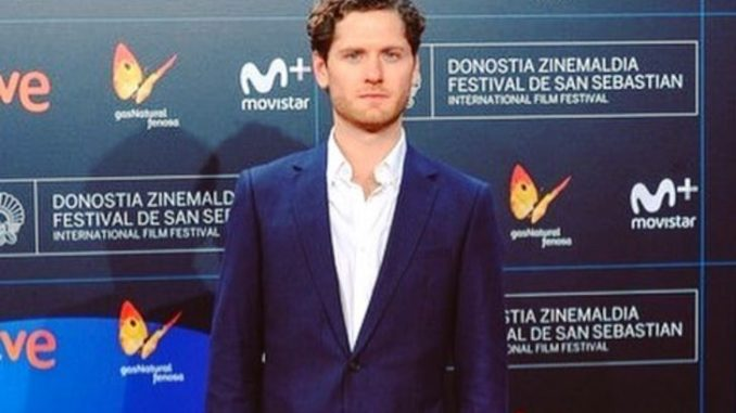 Kyle Soller in a dark blue suit at an event.