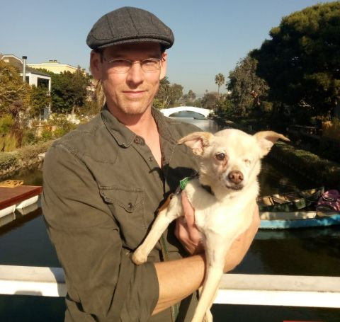 A man in a green shirt and a cap holding a dog.