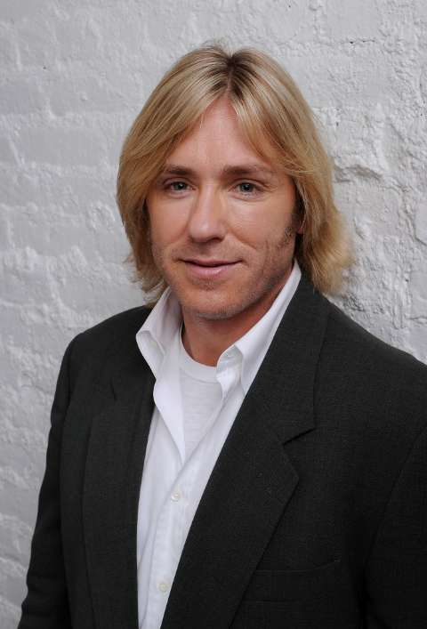 Actor, Ron Eldard giving a pose in a black coat and white shirt.