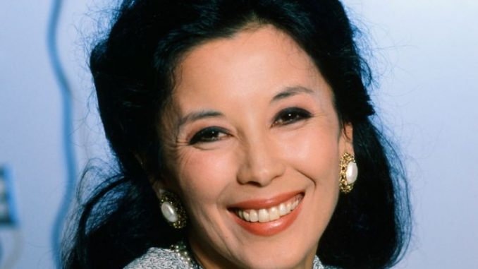 A woman with a black hair and drop earrings.