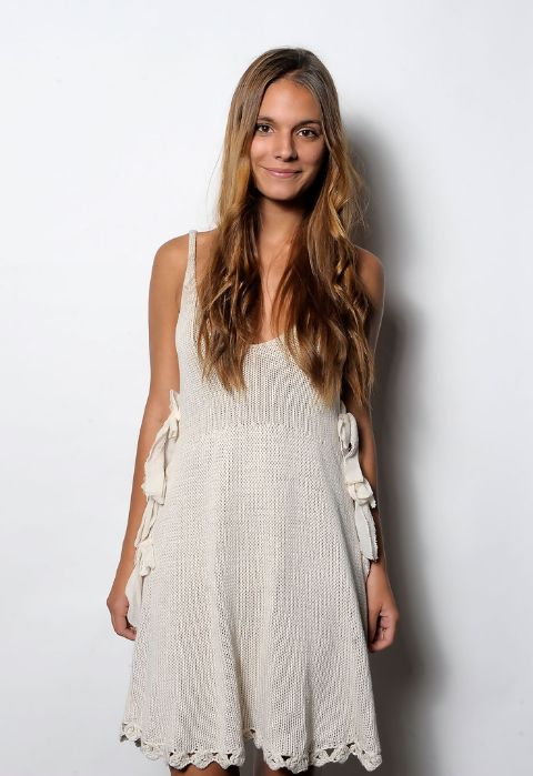 Actress, Caitlin Stasey giving a pose while wearing a white dress