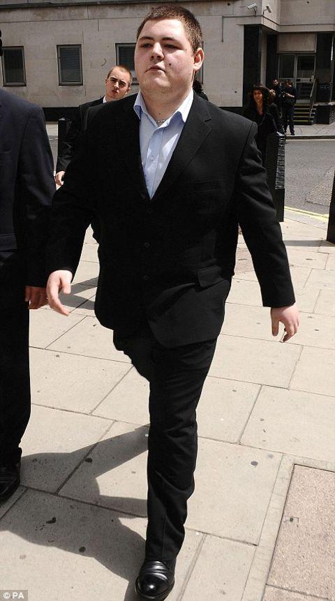 Jamie Waylett walking in street while wearing a black tuxedo.