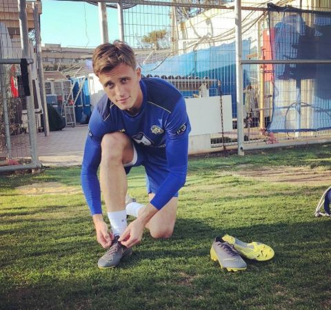 Aaron Schoenfeld getting ready for training ,tying his boots.