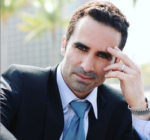 Nestor Carbonell in a black suit and blue tie.