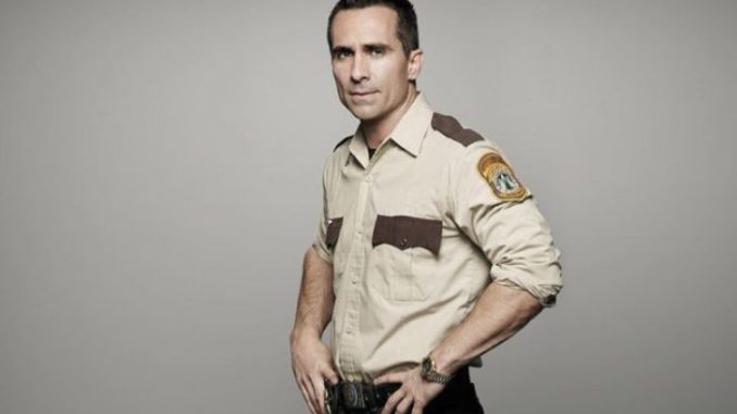 Nestor Carbonell in a police costume.