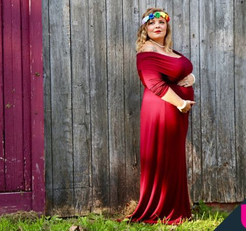 Catelynn Baltierra in a red dress poses while being pregnant.