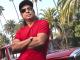 Bikram Choudhury posing in a red t-shirt and black cap.