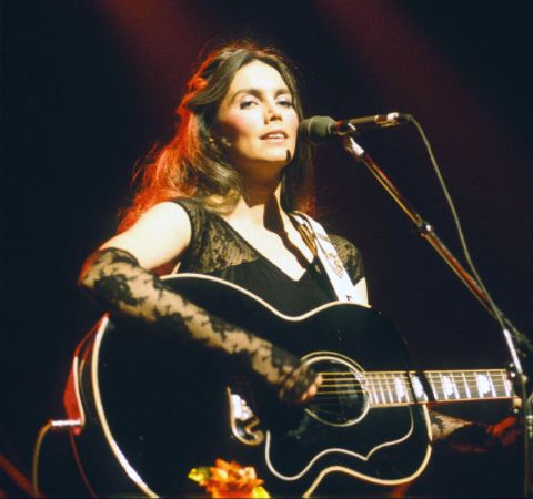 Emmylou Harris singing at a concert with her guitar.