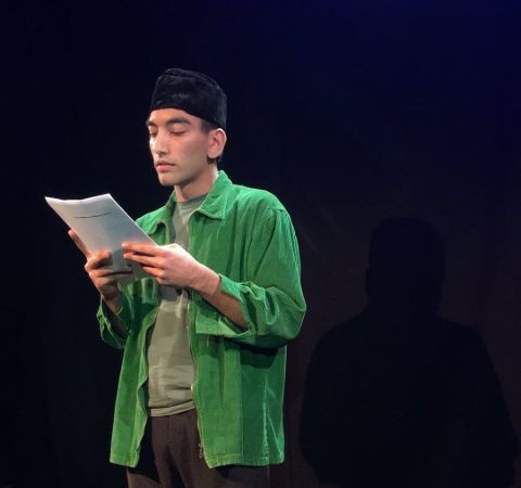 Nabhaan Rizwan reading his lines at a stage.