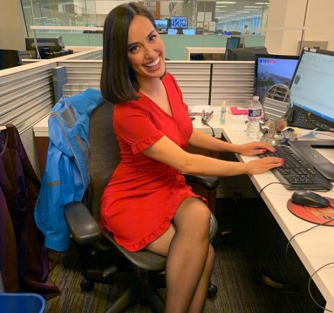 Katie Katro in a red dress in front of her PC.