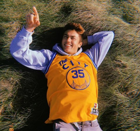Kelly Wakasa in a yellow t-shirt lying at a meadow.