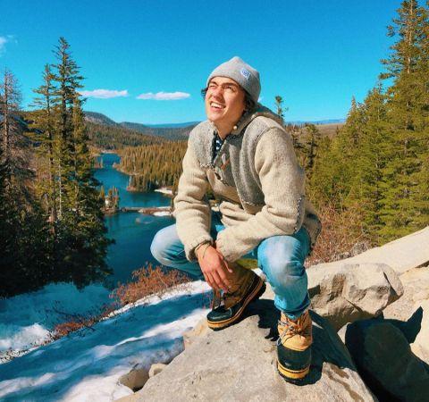 Kelly Wakasa in a grey t-shirt poses at a beautiful scenery.