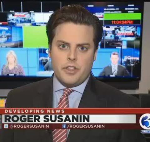 Roger Susanin in a black tux reporting a news on live television.