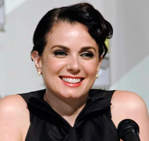 Mia Kirshner in a black t-shirt at an interview.