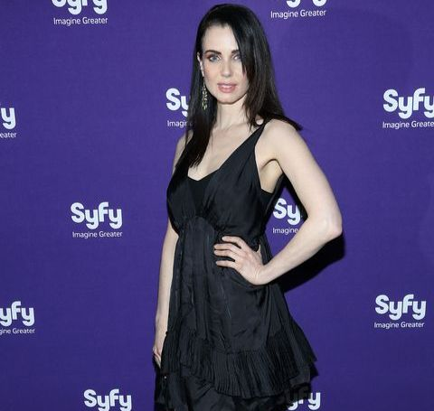 Mia Kirshner in a black dress poses for a picture.