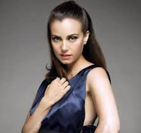 Mia Kirshner in a black dress poses for a photoshoot.