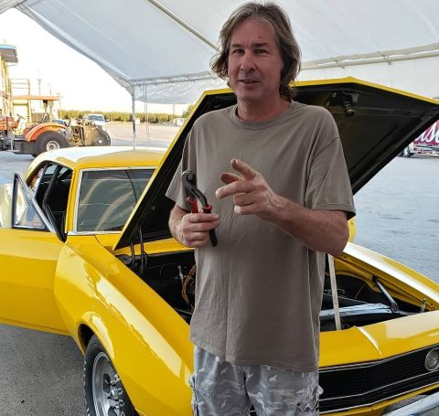 Steve Dulcich poses in front of a yellow car.