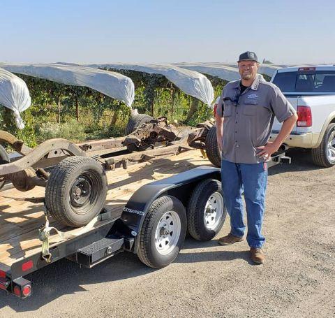 Steve Dulcich in a grey t-shirt poses besides a repairing truck.