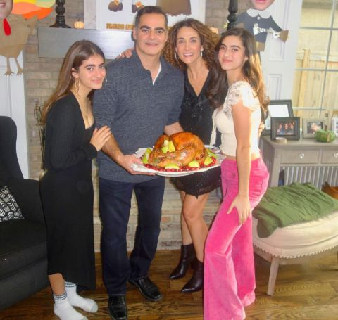 Peter Constantinides in blue shirt with his wife and daughters.