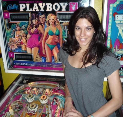 Jenna Morasca in a grey outfit poses before a playboy magazine stand.