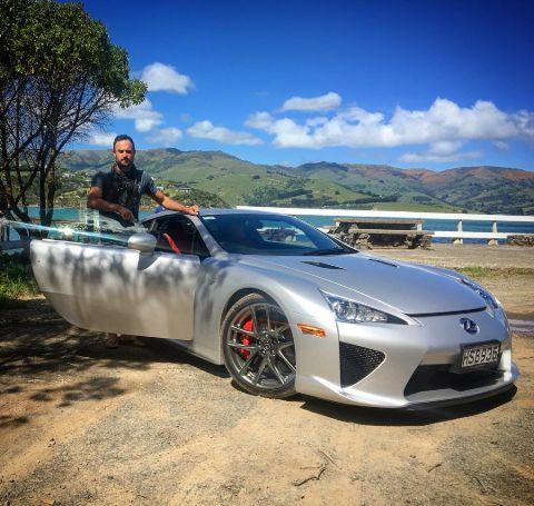 Jordan Mauger poses besides his grey lexus car.