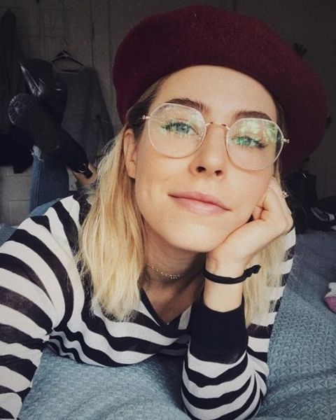 Alexandra Turshen taking a selfie while putting her glasses on.