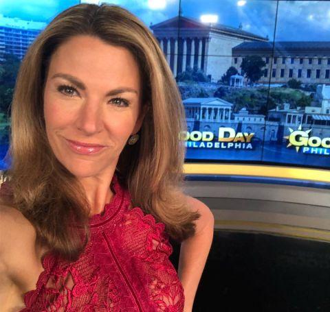 Fox 29's Karen Hepp in a red dress poses a selfie.