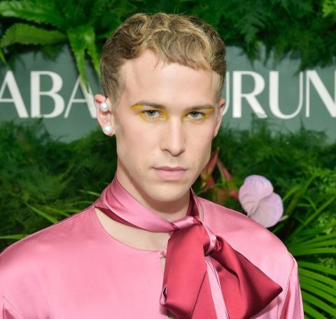 Tommy Dorfman in a pink outfit poses during a photoshoot.