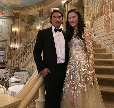 Elizabeth Vasarhelyi in a white gown besides her  husband Jimmy Chin poses for a picture.