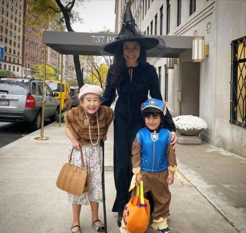 Elizabeth Vasarhelyi in a black outfit poses with her children in Halloween 2019.