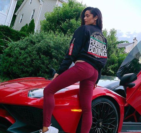 Janira Kremets poses alongside a red Lamborghini.