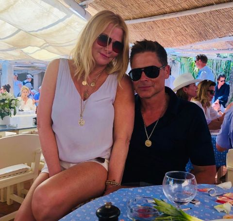 Sheryl Berkoff in white sitting in the lap of husband Rob Lowe.