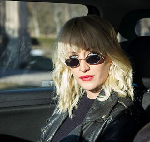 Julia Ragnarsson in a black leather jacket poses in the car.