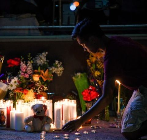 A kid lights candle in Khaseen Morris's memorial service.