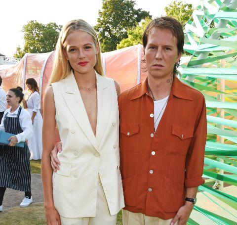 Alan Pownall in a orange shirt poses alongside the gorgeous Gabriella Wilde.
