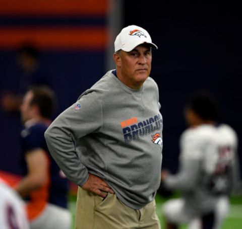 Vic Fangio looks at the game from sidelines in Denver Broncos's grey t-shirt.